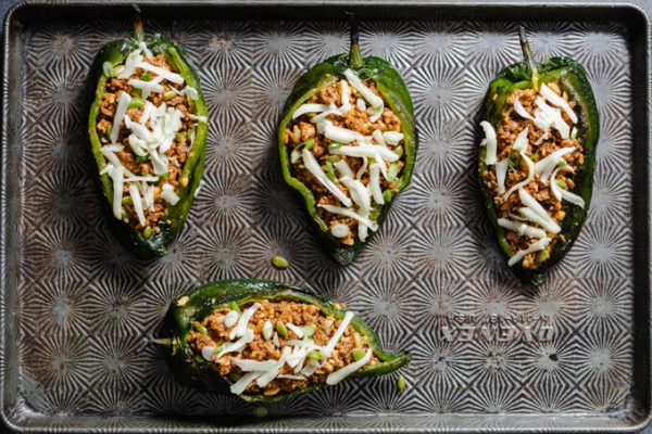 Poblano peppers stuffed with ground beef on a sheet pan before baking.