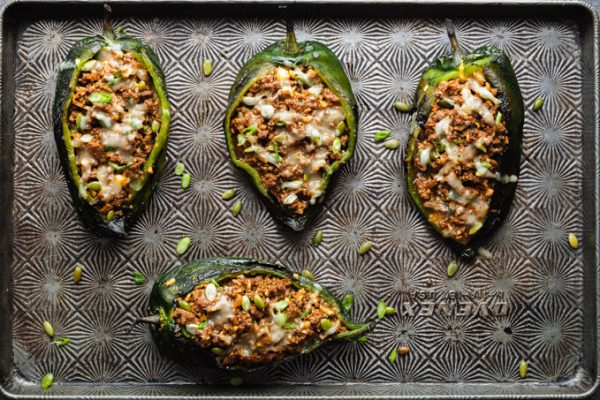Stuffed poblano peppers on a sheet pan after baking.