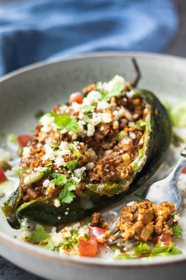 Stuffed poblano peppers with cheese and cilantro on a plate with fork.