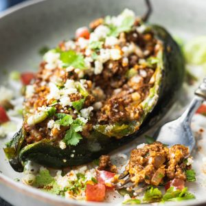 Ground beef stuffed poblano peppers with cheese on a plate with fork.