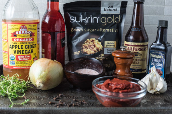 Ingredients for keto BBQ sauce: vinegar, onion, garlic, thyme, low carb sweetener, Worcestershire sauce, liquid smoke, black pepper, tomato paste and clove.
