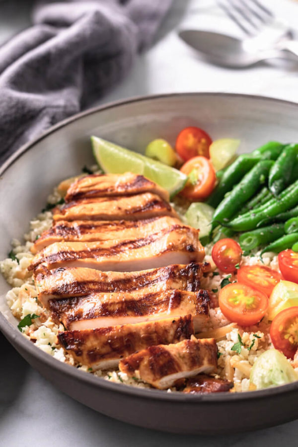 Sliced Key West chicken breast on cauliflower pilaf with vegetables in a bowl.