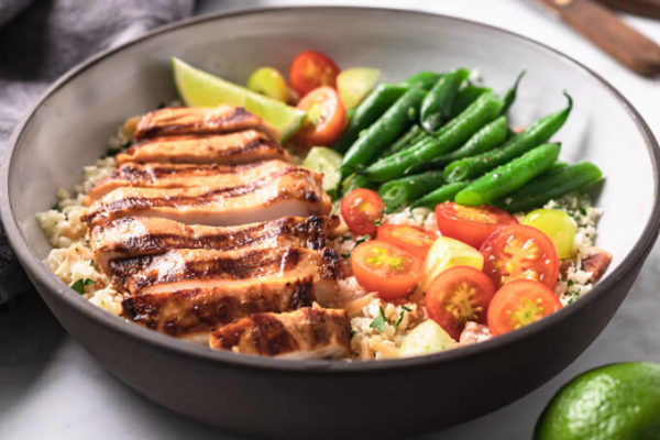 Grilled Key West chicken in a bowl with vegetables and a lime wedge.