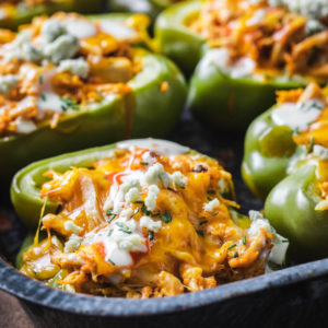 Buffalo Chicken Stuffed Peppers with ranch dressing and crumbled blue cheese in a casserole dish