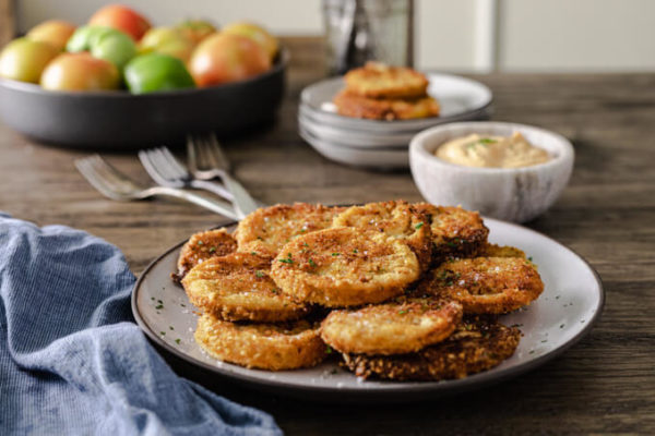 Crispy fried green tomatoes on a plate with dipping sauce