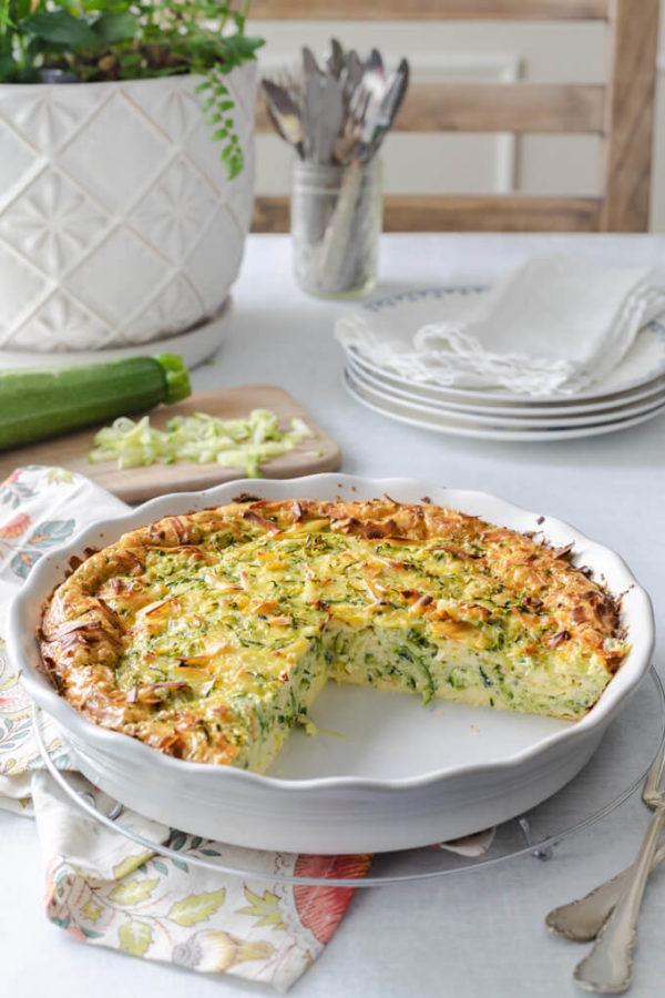 zucchini quiche in a quiche dish with grated zucchini