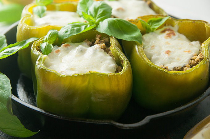 Green peppers in a cast iron skillet stuffed with ground chicken with cheese on top