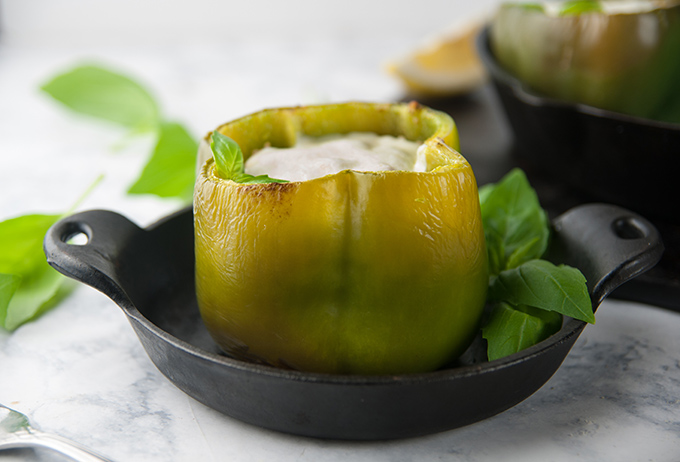 A green pepper stuffed with chicken and cheese in a small serving skillet in front of a larger skillet of stuffed peppers on a light background