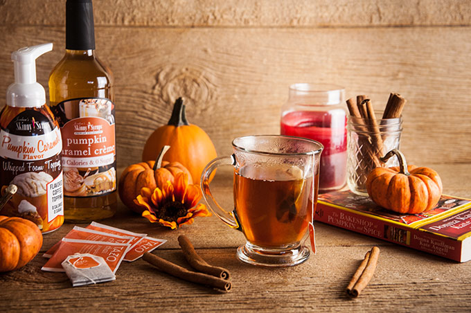 A cup of tea steeping with cinnamon stick s, pumpkins, and florals and pumpkin spice syrup on wood