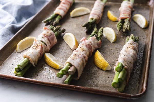 Bacon wrapped asparagus bundles and cut lemons on a sheet pan