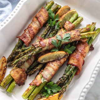 Bacon wrapped asparagus bundles with roasted lemons in a white serving dish