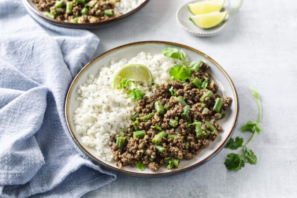 low carb beef keema with cauliflower rice on a plate with cilantro and limes