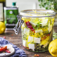 Marinated feta with herbs, lemon zest, red pepper and olive oil in a glass