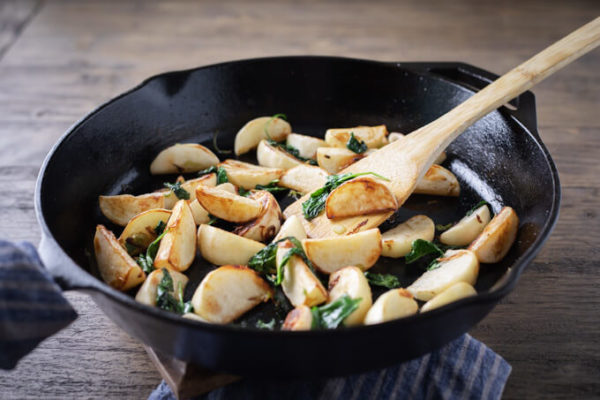 Cooked pan fried turnips in a pan with spinach and a bamboo spatula
