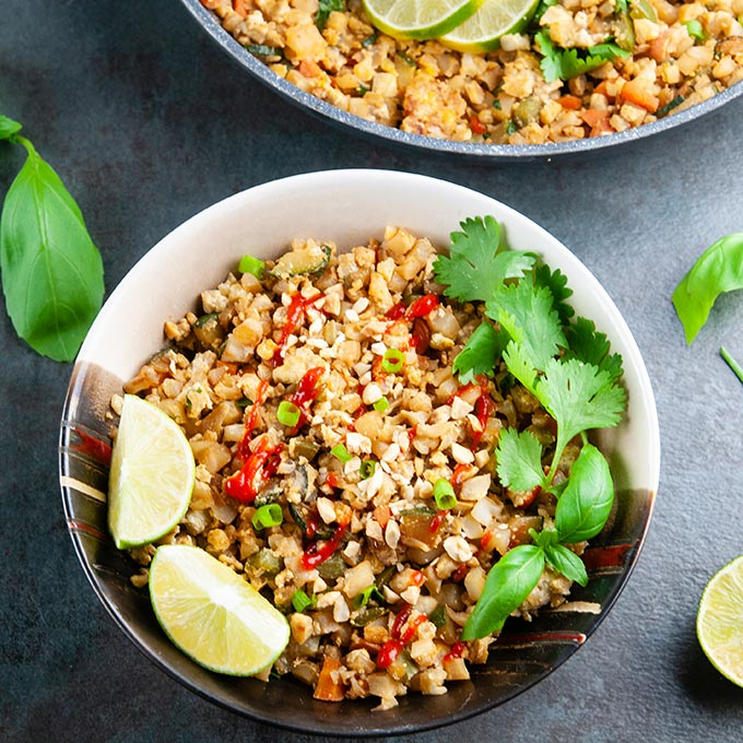 A bowl and a pan full of cauliflower fried rice on a dark background