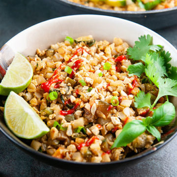 A bowl of Thai basil cauliflower fried rice on a dark background with lime wedges and cilantro as garnish