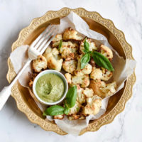 Roasted cauliflower florets in a bowl with pesto dipping sauce, basil and a fork