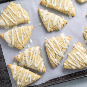 Low Carb Lemon Poppy Seed Scones with lemon glaze on parchment lined sheet pan