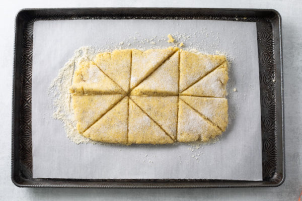 Lemon Poppy Seed Scones cut into triangles on a sheet pan.