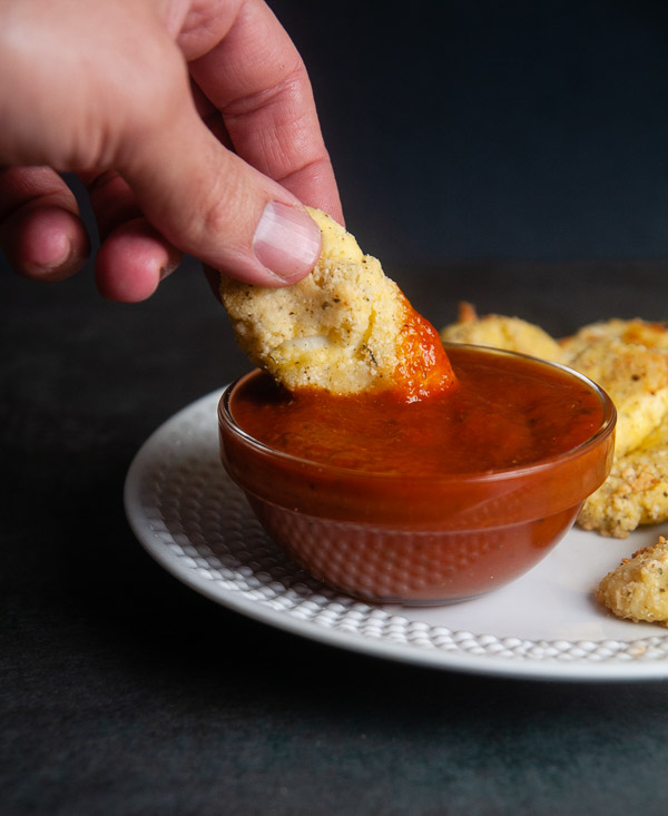 Hand dipping a low carb mozzarella stick into a bowl of sauce on a black background