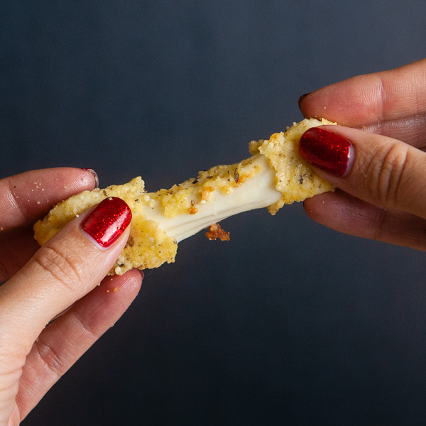 Low carb mozzarella stick being stretched apart by two female hands, showing a gooey cheese pull on black