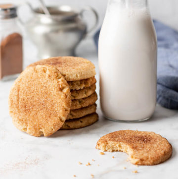 keto snickerdoodle cookies with cinnamon stacked by a bottle fo milk