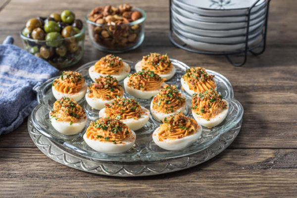 Platter of keto deviled eggs with bowls of olives and nuts with appetizer plates