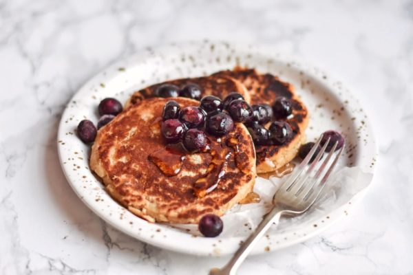 Keto vegan coconut flour pancakes with blueberries on a plate with fork
