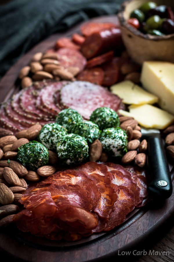 Charcuterie board with cured meats, herbed goat cheese balls, hard cheese, almonds and marinated olives
