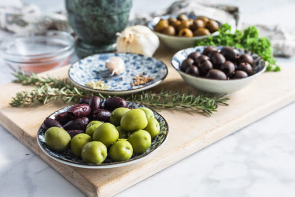 Marinated olives ingredients: assorted olives, spices, garlic, rosemary and parsley