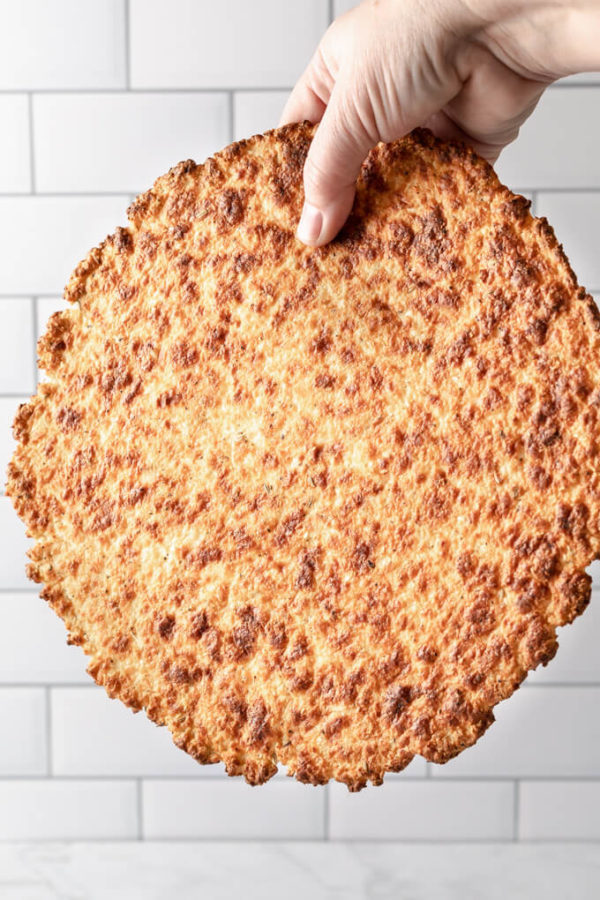 crispy keto cauliflower pizza crust held in one hand