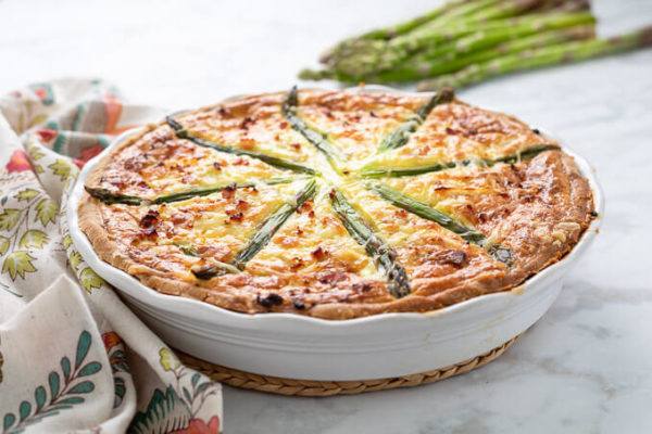 Ham and asparagus quiche in white ruffled pie plate with colorful napkin and asparagus spears.