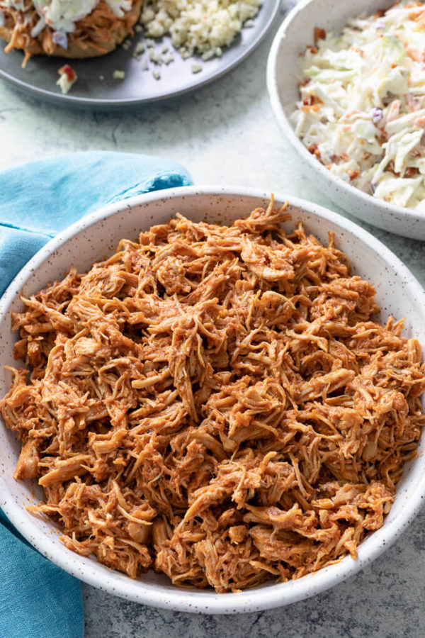 Bowl of pulled BBQ chicken with a bowl of coleslaw and blue napkin.