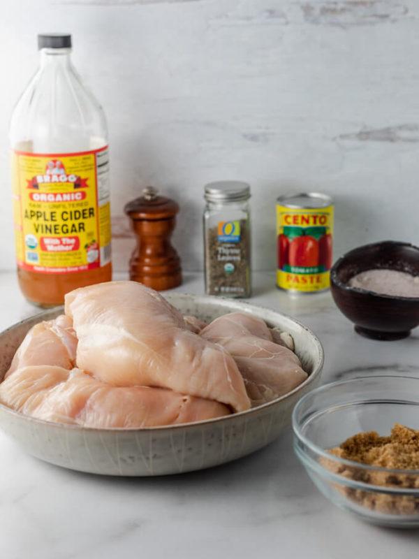 Crockpot BBQ chicken ingredients: vinegar, salt, pepper, tomato paste, chicken, herbs and spices.