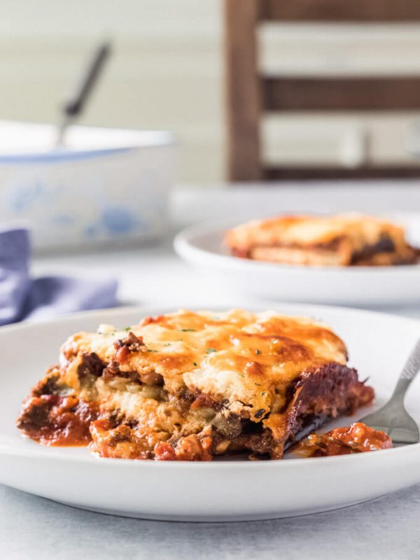 Plates of keto eggplant lasagna with forks on a table with lasagna pan and chair in background
