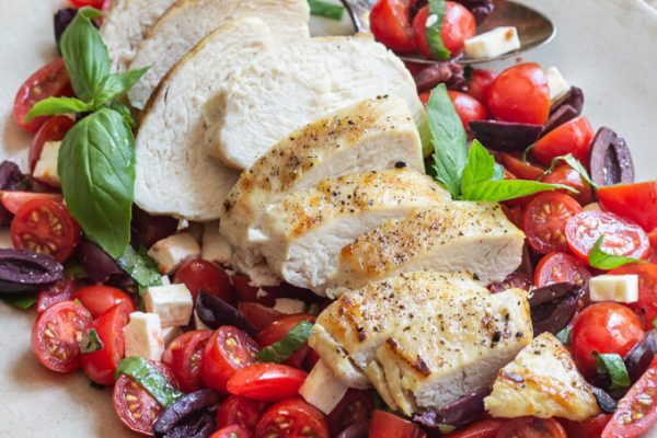 Sliced grilled chicken on a tomato salad including basil, mint, kalamata olives and feta cheese.