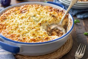 keto shepherd's pie with browned cheesy cauliflower topping with spoon.