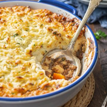 Baked keto cottage pie with mashed cauliflower topping in blue rimmed casserole dish with spoon.