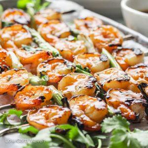 Keto teriyaki shrimp skewers with scallions glistening with sauce.