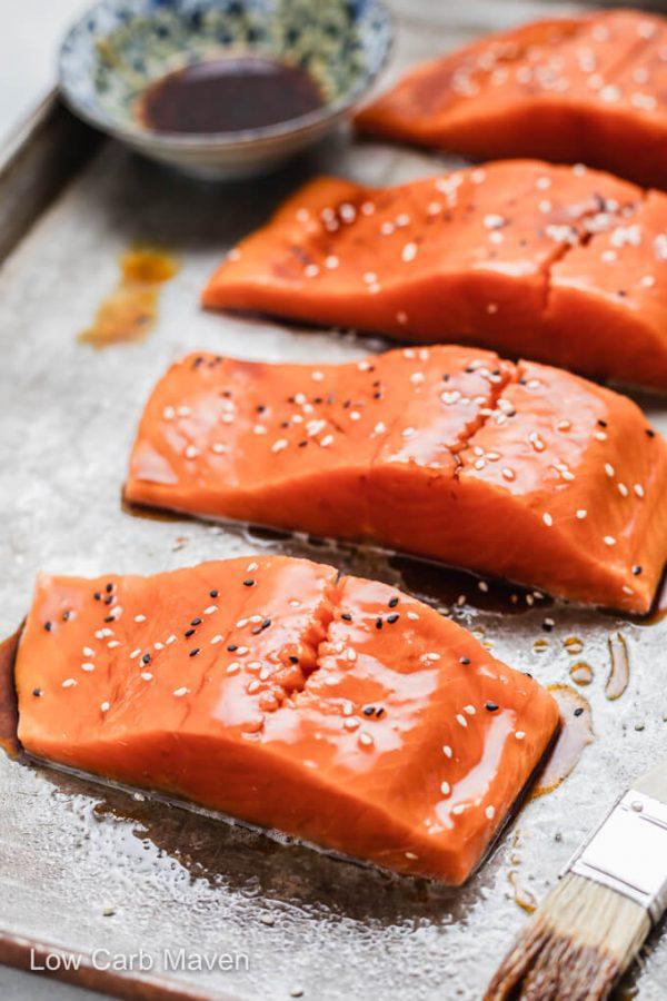 Raw salmon filets with keto teriyaki glaze and sesame seeds on sheet pan with bowl of sauce and pastry brush.