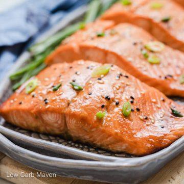 Keto salmon teriyaki filet topped with sesame seeds and sliced scallions on gray platter.