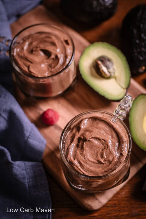 Two keto chocolate avocado puddings in cups with halved avocado on a cutting board with blue napkin to side