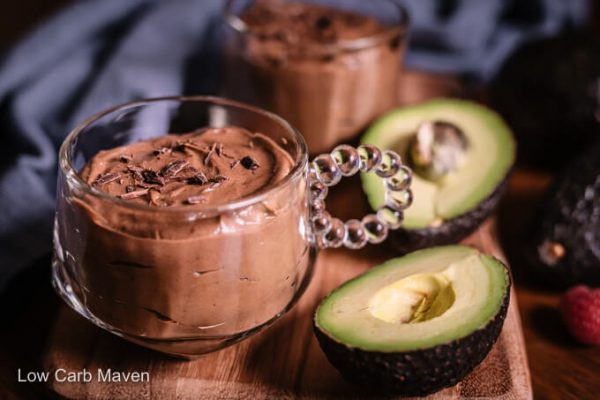 Creamy keto chocolate avocado pudding in cup with halved avocado and napkin behind.